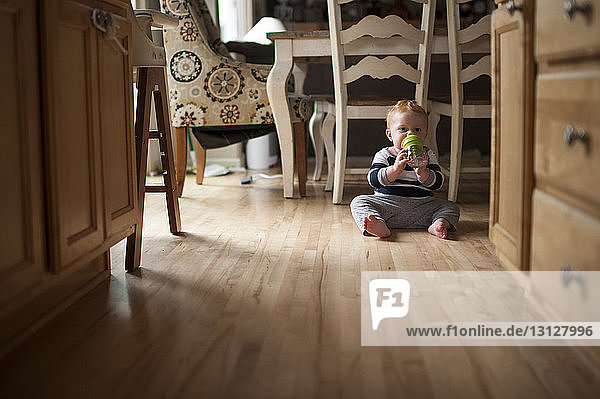 Portrait of baby boy drinking water from bottle while sitting on floor at home