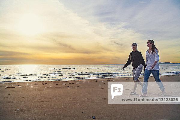 Glückliche Mutter und Tochter gehen bei Sonnenaufgang am Strand gegen den Himmel