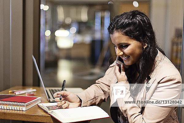 Happy woman talking on phone while writing in book at table