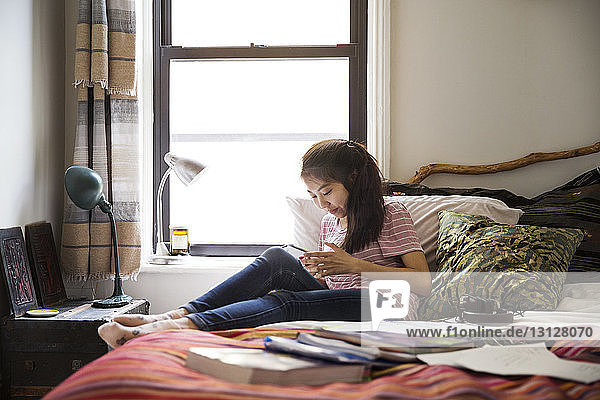 Teenage girl using smart phone while relaxing on bed