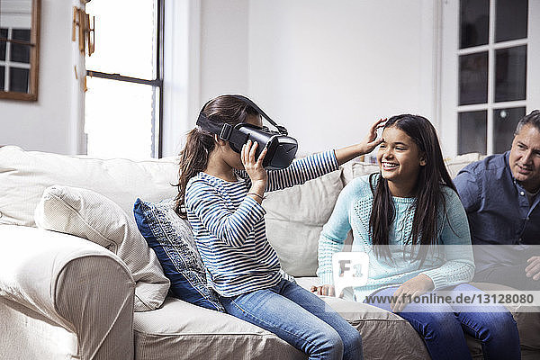 Father and daughter looking at girl wearing virtual reality simulator while sitting at home