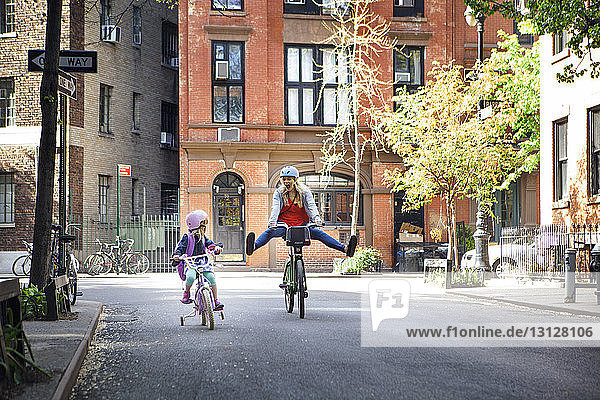 Cheerful woman riding bicycle with daughter on street