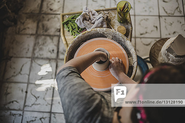 High angle view of potter using pottery wheel to make clay pot at workshop
