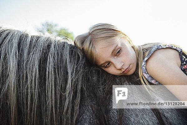 Seitenansicht eines nachdenklichen Mädchens auf einem Pferd vor klarem Himmel