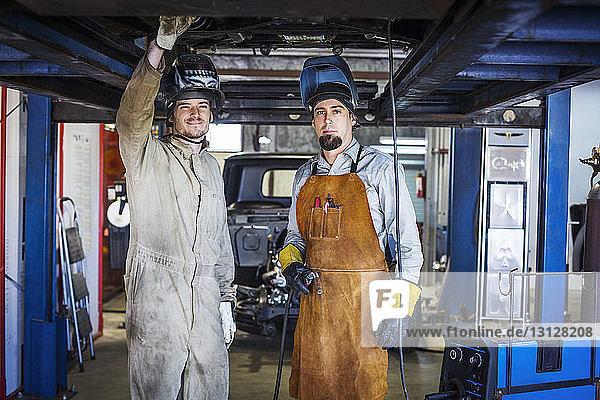 Portrait of mechanics standing under car in auto repair shop