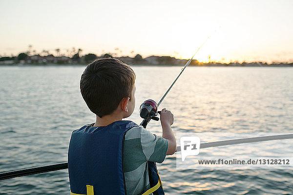 Junge fischt im Meer  während er auf einem Boot steht