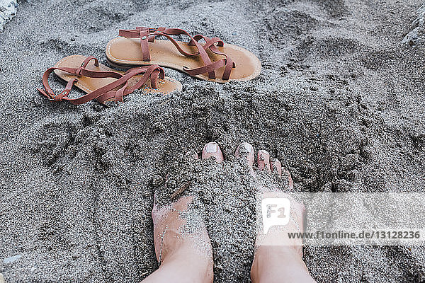 Cropped legs of girl in sand at beach
