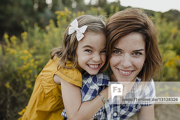 Portrait of cheerful mother and daughter against plants at field