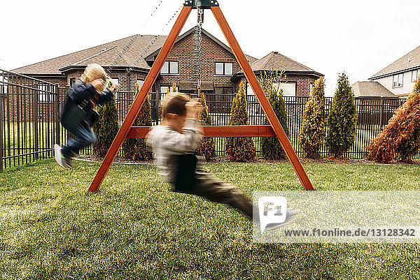 Boys playing on swings at yard