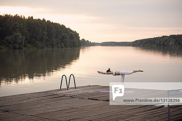 Frau  die Kriegerin 3 übt  posiert auf dem Pier am See vor bewölktem Himmel bei Sonnenuntergang