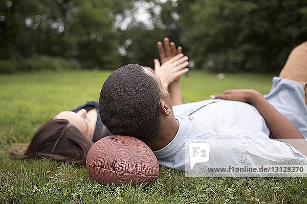 Mann ruht mit dem Kopf auf dem Fussball  während er mit der Frau auf dem Feld liegt