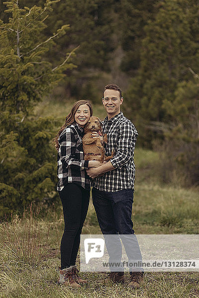 Portrait of smiling young couple carrying dog while standing on grassy field