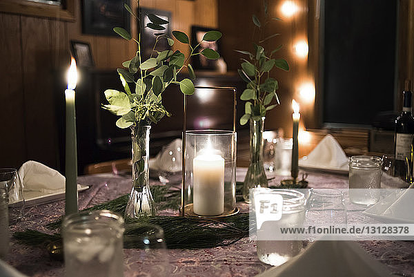 Close-up of lit candles decorated on dining table at home
