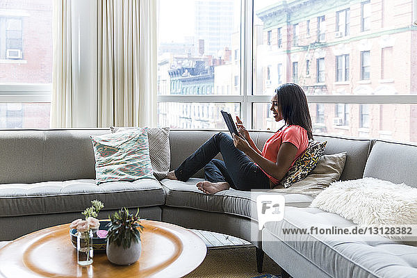Full length of woman using tablet computer while resting on sofa against window at home