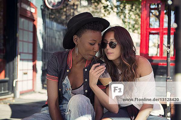 Freundinnen genießen Smoothie im Straßencafé