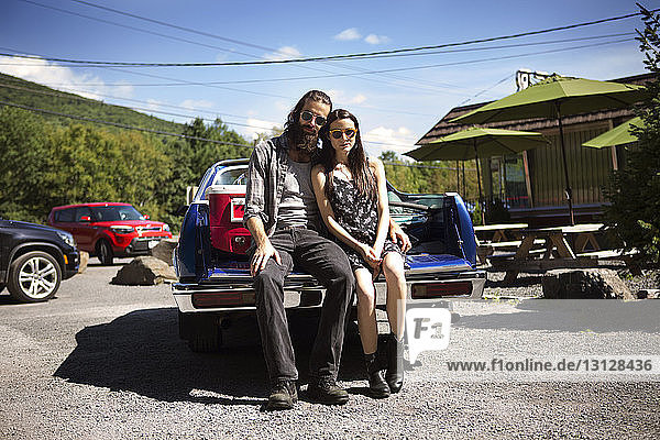 Portrait of confident couple sitting on pick-up truck against sky