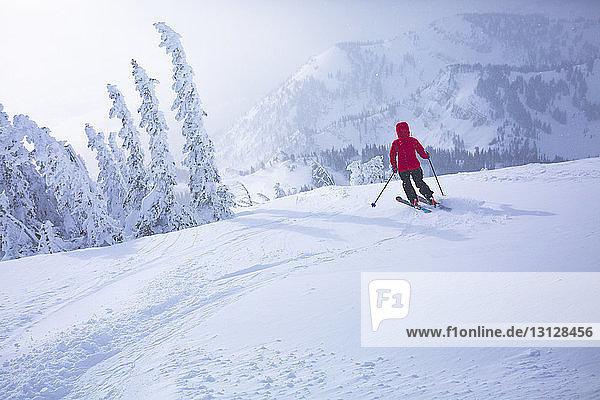 Rückansicht einer Frau beim Skifahren in schneebedeckter Landschaft