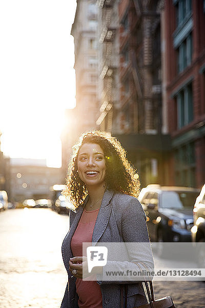 Happy businesswoman looking away while standing on city street