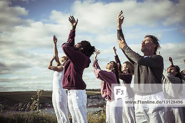 Menschen trainieren auf dem Feld gegen bewölkten Himmel