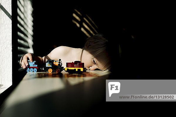 Boy playing with toy train while sitting at table by window