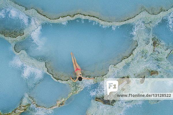 High angle view of teenage girl wearing bikini while relaxing in hot spring
