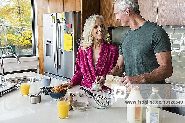 Lächelnder Mann schaut Frau an  während er in der Küche Essen zubereitet
