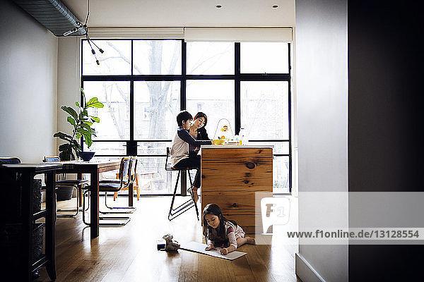 Mutter hilft dem Sohn bei den Hausaufgaben  während die Schwester zu Hause auf dem Boden lernt