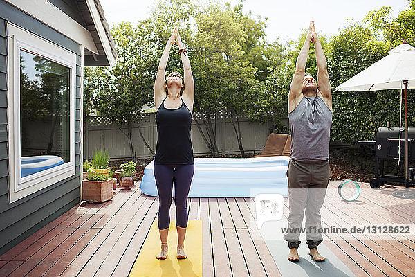 Paar praktiziert Yoga im Hinterhof an einem sonnigen Tag