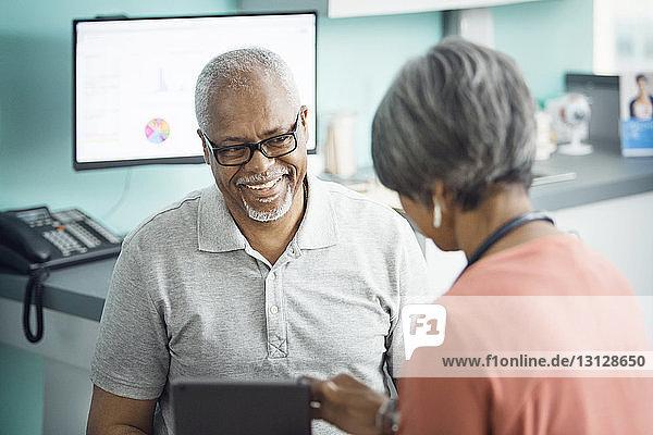Glücklicher älterer männlicher Patient im Gespräch mit einer Ärztin in der Klinik