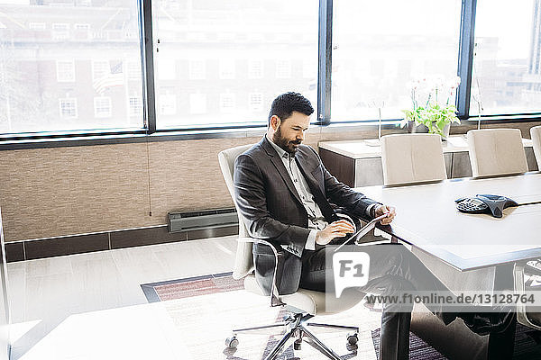 Businessman using tablet computer in board room at office