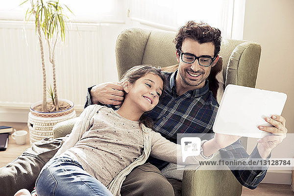 Affectionate father and daughter looking at digital tablet while sitting on chair