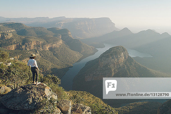 Rear view of woman looking at mountains while standing on rock against sky during sunset