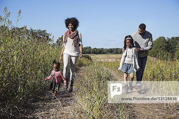 Happy family walking on grassy field against blue sky
