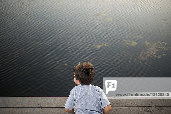 High angle view of boy lying on pier over lake at park