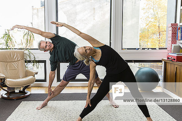 Couple stretching while practicing yoga at home