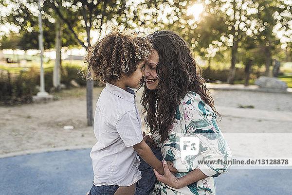 Lächelnde Mutter spielt mit Sohn im Park
