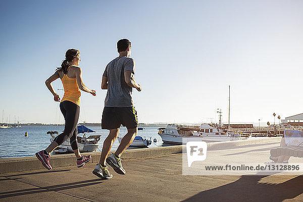 Rückansicht von männlichen und weiblichen Athleten beim Joggen auf dem Pier am Hafen