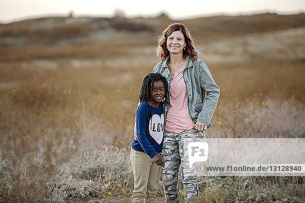 Porträt einer Mutter mit Tochter auf einem Grasfeld im Wald stehend