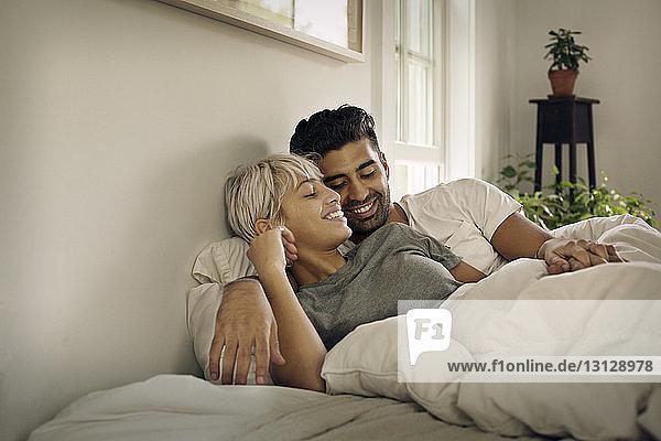 Glückliches junges Paar liegt zu Hause im Bett