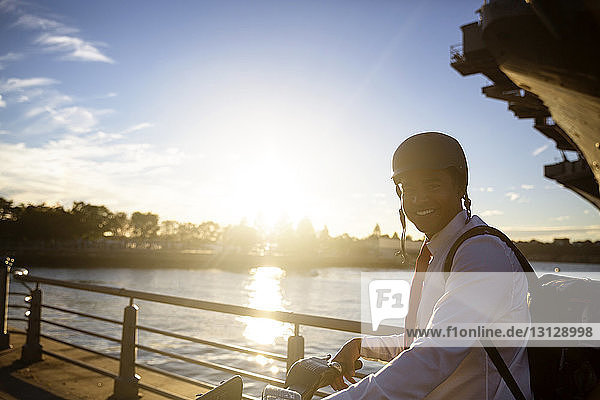 Portrait of businessman with bicycle standing against river during sunset