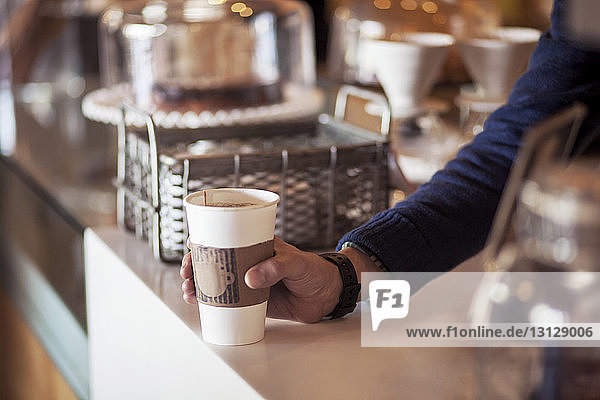 Cropped image of barista holding disposable cup at counter in cafe