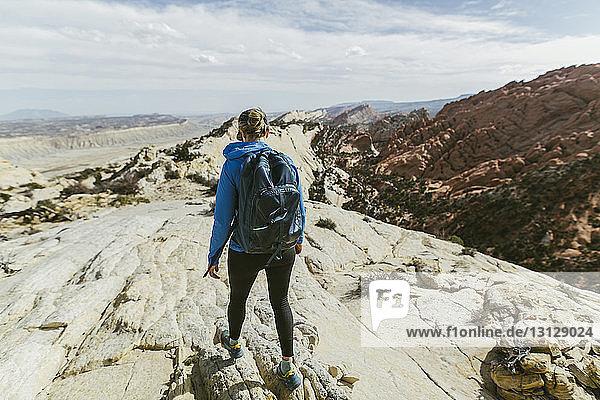 Rückansicht einer Wanderin mit Rucksack  die an einem sonnigen Tag auf einem Felsen geht
