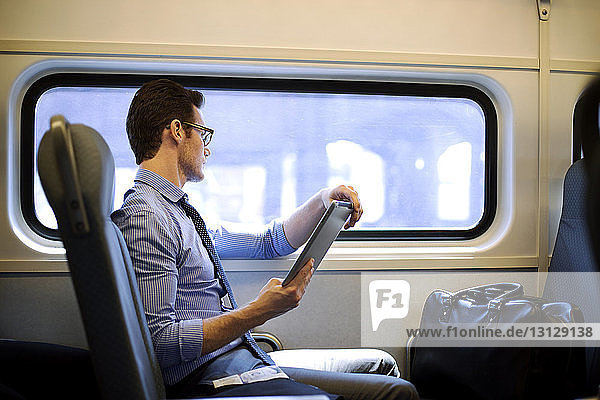 Side view of businessman holding tablet computer while traveling in train