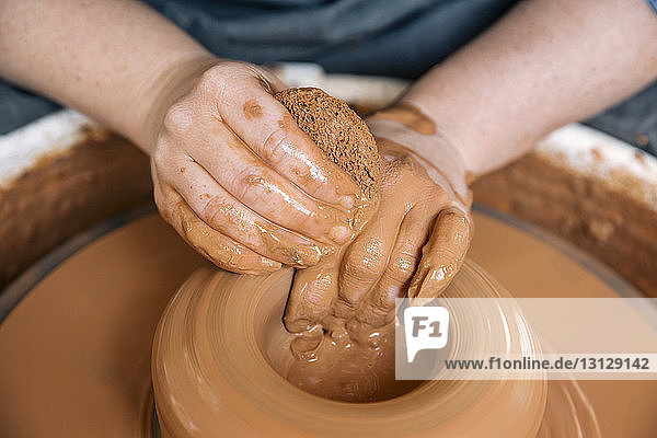 Close-up of woman's hands molding clay on wheel