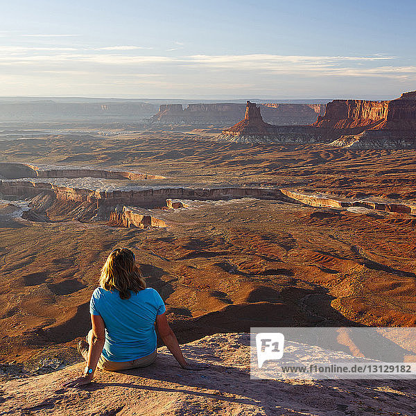 Female hiker looking at view while sitting on rock at Canyonlands National Park