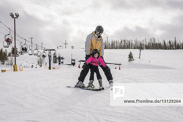 Vater mit Tochter beim Skifahren in schneebedeckter Landschaft vor bewölktem Himmel