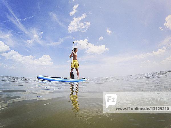 Shirtless teenage boy paddleboarding on sea against sky