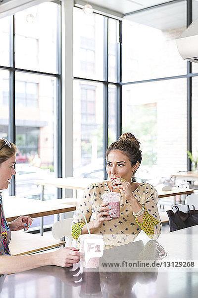 Frau sieht Freundin an  während sie im Café Saft trinkt