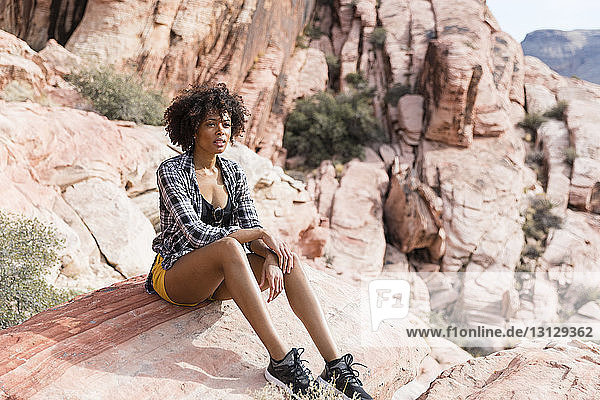 Thoughtful woman looking away while sitting on rock formation during sunny day