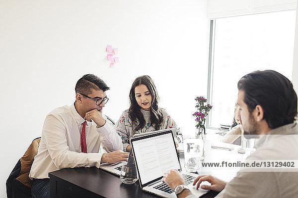Kollegen diskutieren  während ein Geschäftsmann einen Laptop am Schreibtisch im Büro benutzt